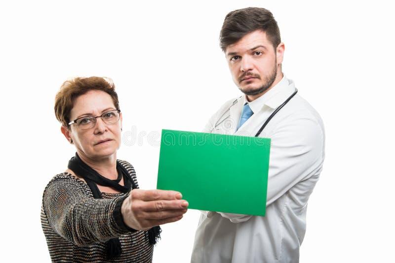 Patient supérieur féminin montrant le conseil vert au docteur masculin images stock