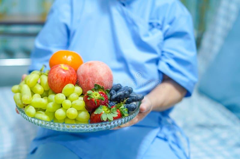 Patient supérieur ou plus âgé asiatique de femme de vieille dame tenant la nourriture saine de divers fruits frais avec espoir et image libre de droits