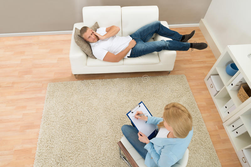 Patient Talking To His Psychiatrist. Patient Lying On Couch In Front Of Psychiatrist Writing On Clipboard royalty free stock photos