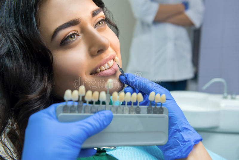 Patient and tooth color chart. Young women smiling. Effective teeth whitening royalty free stock photos