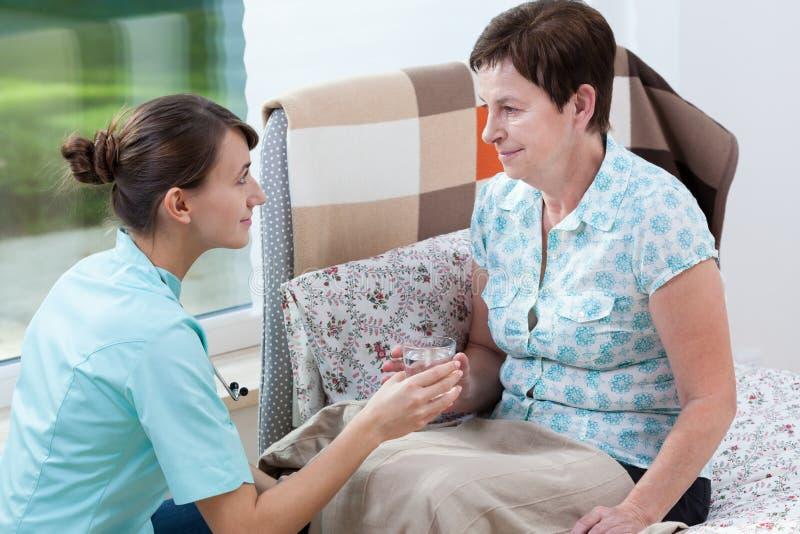 Patient und Glas Wasser stockbild