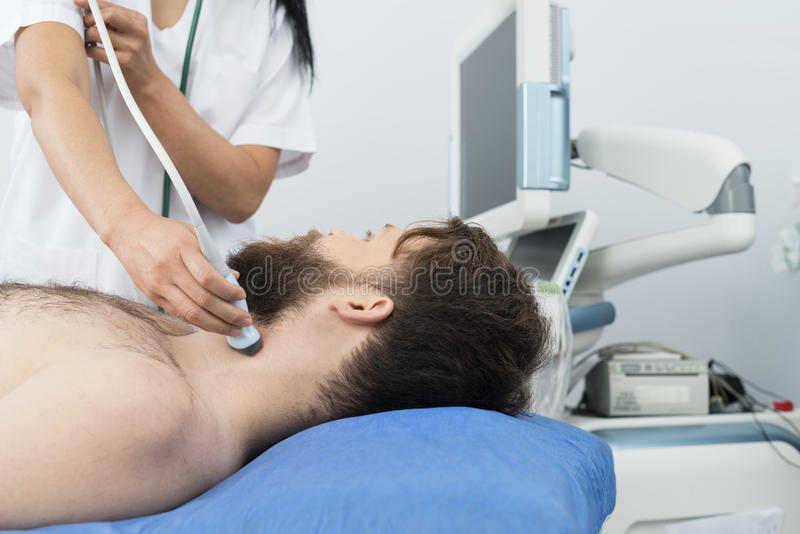 Patient Undergoing Ultrasound Of Thyroid From Doctor. Male patient undergoing ultrasound of thyroid from female doctor in hospital stock photo