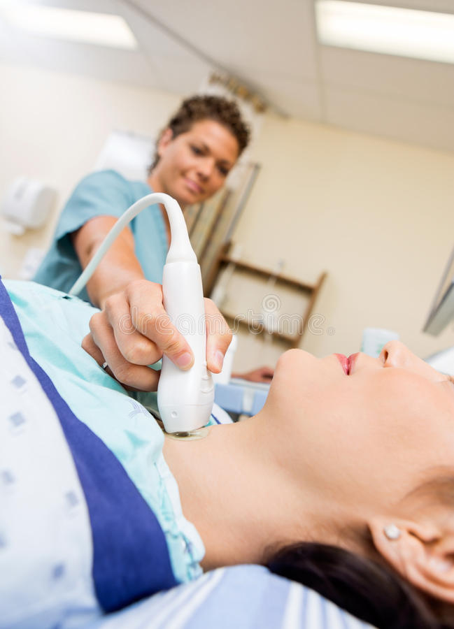 Patient Undergoing Ultrasound Of Thyroid Gland. Female patient undergoing ultrasound of thyroid gland in hospital room royalty free stock photography