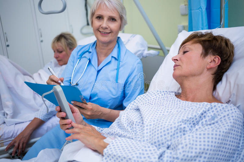 Patient using medical device and nurse sitting next to the bed stock photography