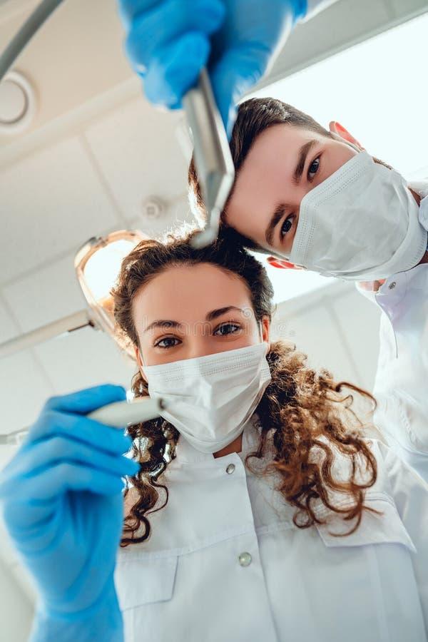 Patient von der zahnmedizinischen Stuhlansicht des Zahnarztes und des Assistenten Ansicht von unten lizenzfreies stockfoto