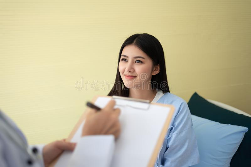 Patiente asiatique de femme pendant le docteur écrivant quelque chose sur un clipboa images libres de droits