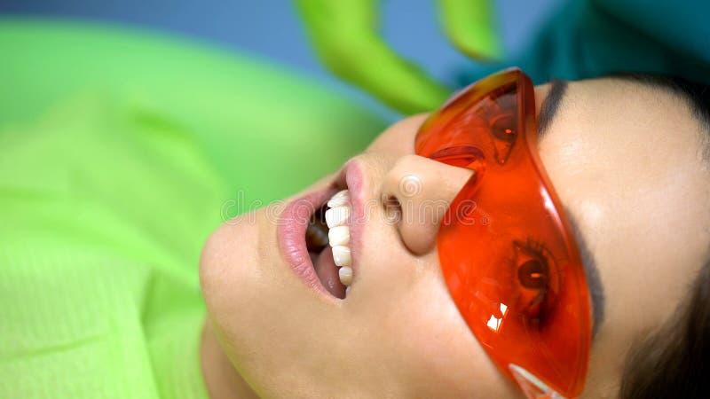 Patiente de femme en verres protecteurs, traitant la lumière pour le traitement moderne de dents images stock