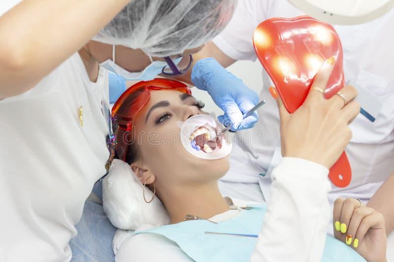 Patiente de fille à la réception au traitement de dentiste de la dent cariqueuse la fille se trouve sur la chaise dentaire avec s photo libre de droits
