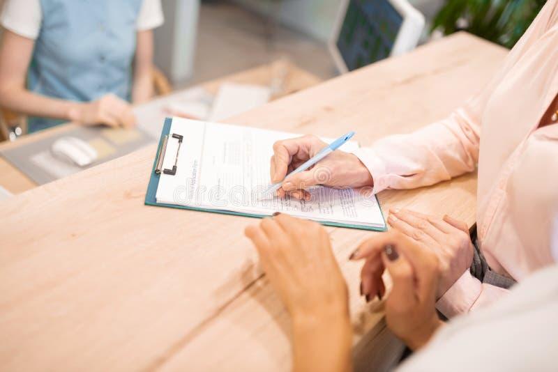 Patiente dentiste remplissant son formulaire de demande médicale photos stock