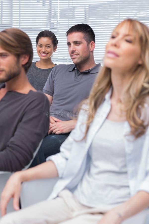 Patienten, die in der Gruppentherapie mit einem Mädchenlächeln hören lizenzfreie stockfotografie