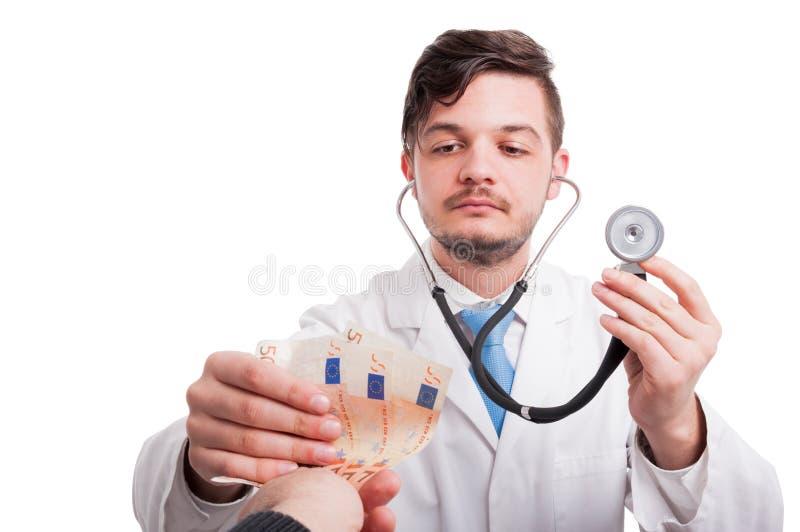 Patienten ger pengar till en doktor royaltyfri bild