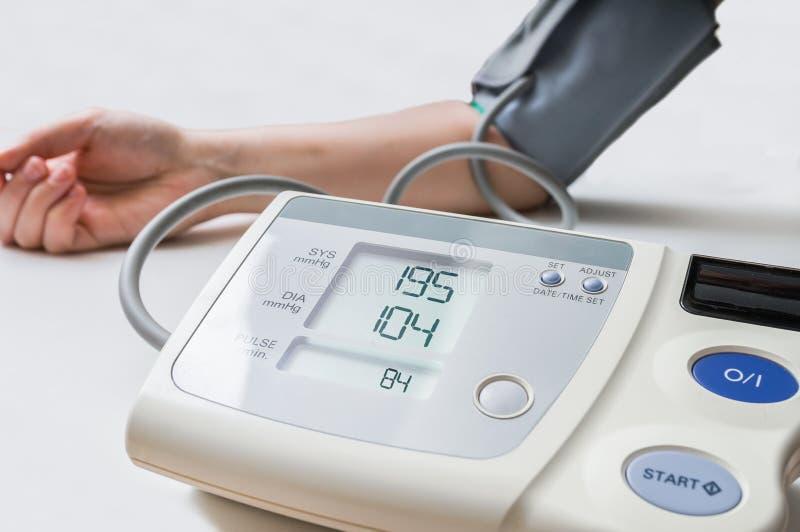 Patienten lider från högt blodtryck Kvinnan mäter blodtryck med bildskärmen arkivfoton