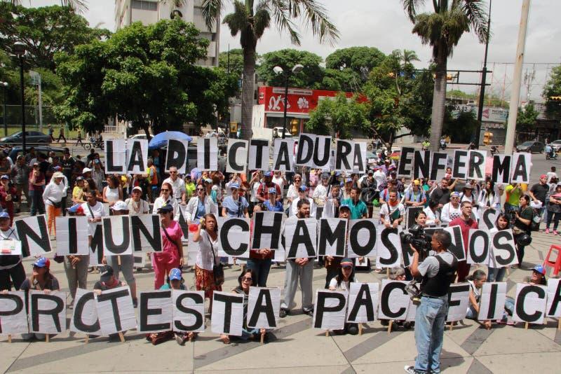 Patienter protesterar över bristen av medicin- och bottenlägelön i Caracas royaltyfri foto