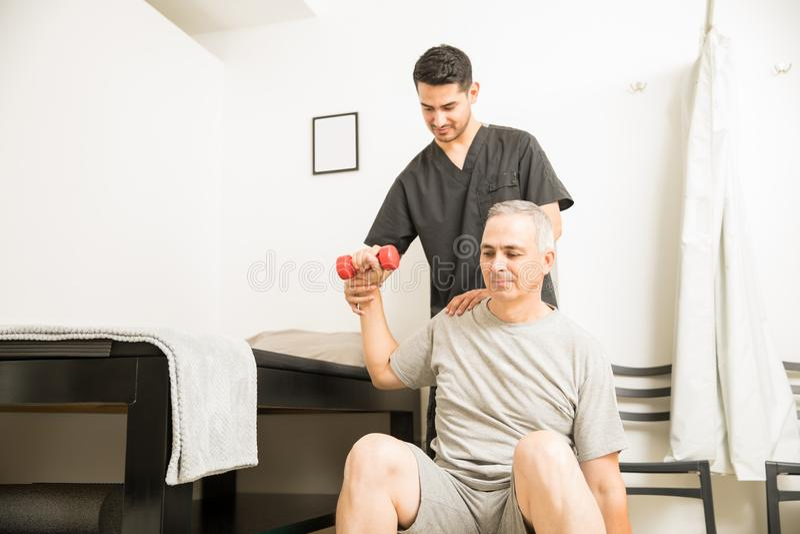 Patientlyftande vikter med hjälp av terapeuten In Physiotherapy fotografering för bildbyråer