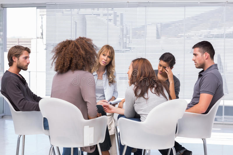 Patients around therapist in group therapy session. Patients around therapist telling their problems in group therapy session royalty free stock photography