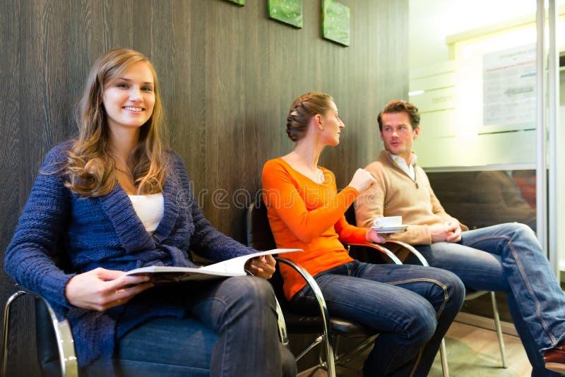 Patients dans la salle d'attente d'un bureau de médecins images libres de droits