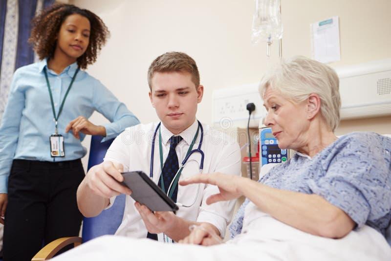 Patients för doktor Sitting By Female säng genom att använda den Digital minnestavlan arkivfoton