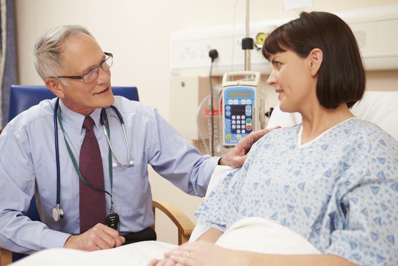 Patients för doktor Sitting By Female säng i sjukhus royaltyfri bild