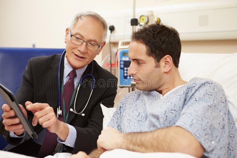 Patients för doktor Sitting By Male säng genom att använda den Digital minnestavlan royaltyfri bild