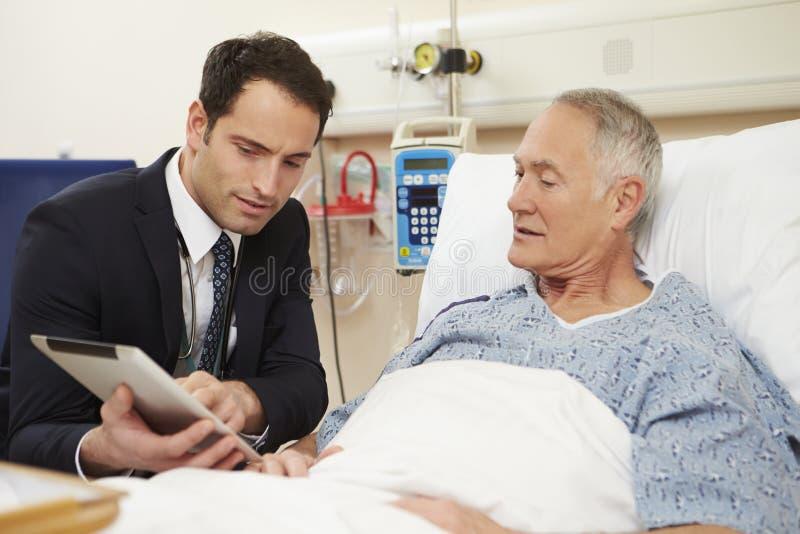 Patients för doktor Sitting By Male säng genom att använda den Digital minnestavlan royaltyfria bilder
