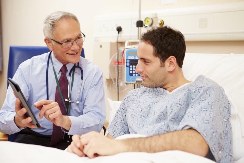 Patients för doktor Sitting By Male säng genom att använda den Digital minnestavlan arkivfoto