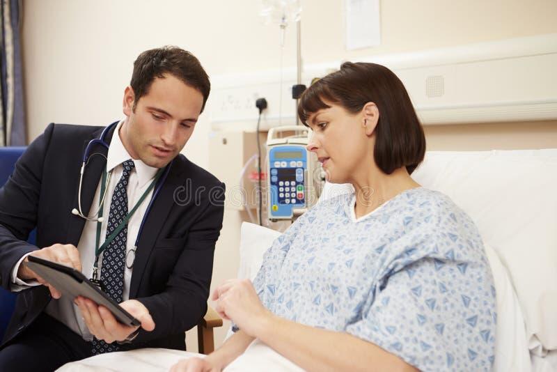 Patients för doktor Sitting By Male säng genom att använda den Digital minnestavlan arkivfoton