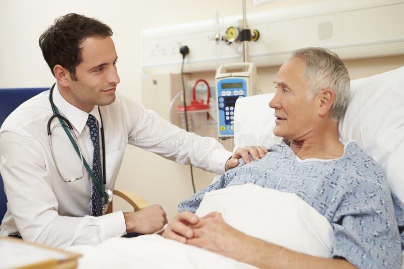 Patients för doktor Sitting By Male säng i sjukhus fotografering för bildbyråer