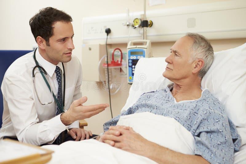 Patients för doktor Sitting By Male säng i sjukhus royaltyfri bild