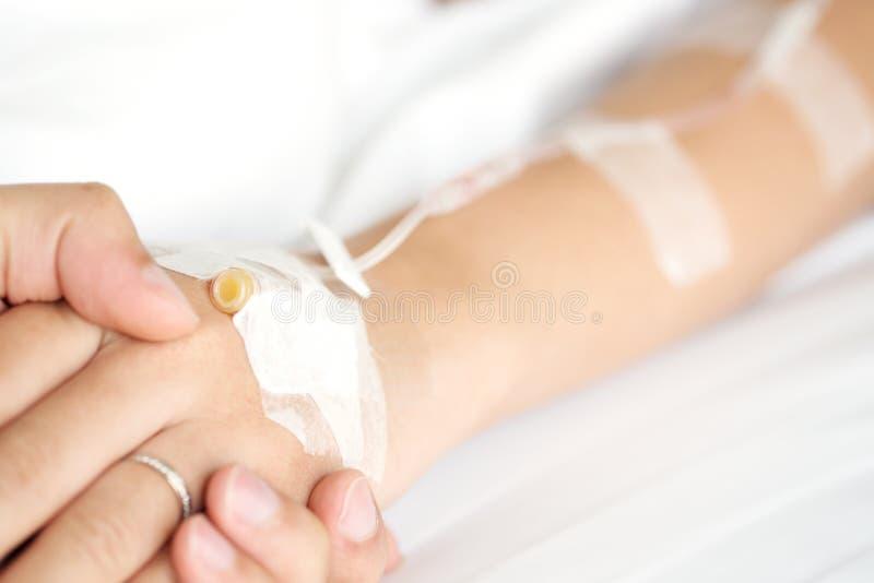 Patients för kvinna för manhand hållande hand på säng i sjukhuset för rea arkivfoton
