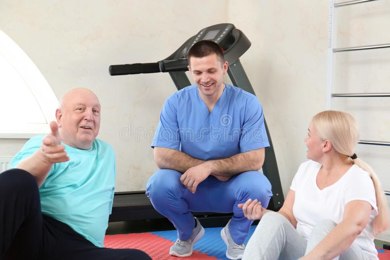 Patients with physiotherapist in rehabilitation center stock images