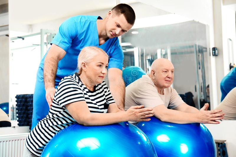 Patients s'exerçant sous la surveillance de physiothérapeute photographie stock