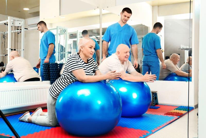 Patients s'exerçant sous la surveillance de physiothérapeute images stock