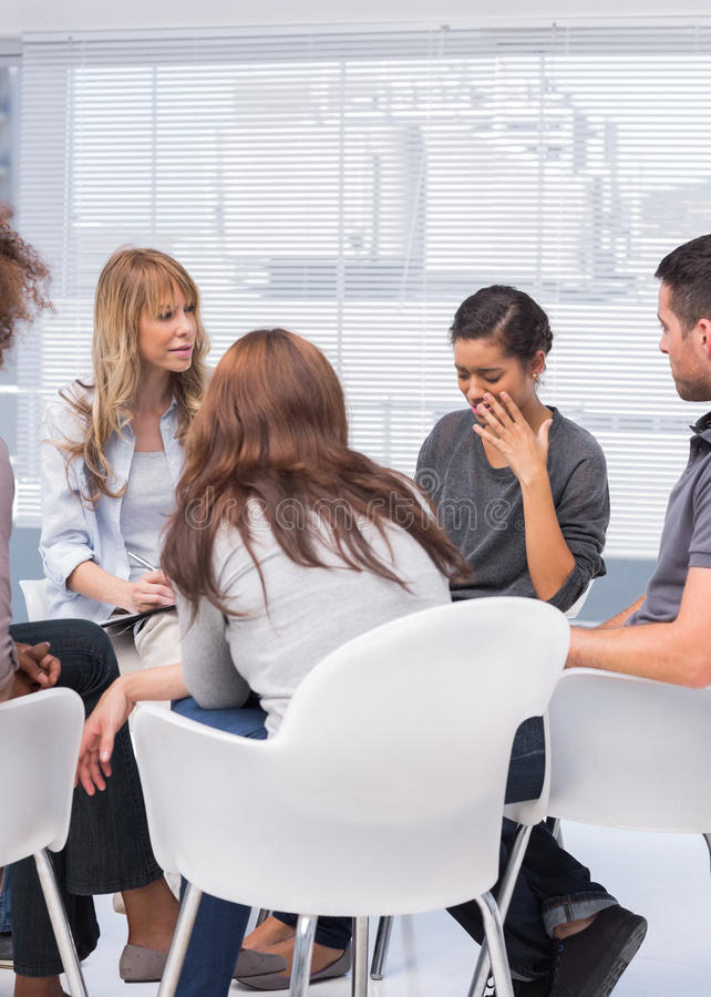 Patients and therapist listening to woman. Patients and therapist listening to women telling her problems royalty free stock photo