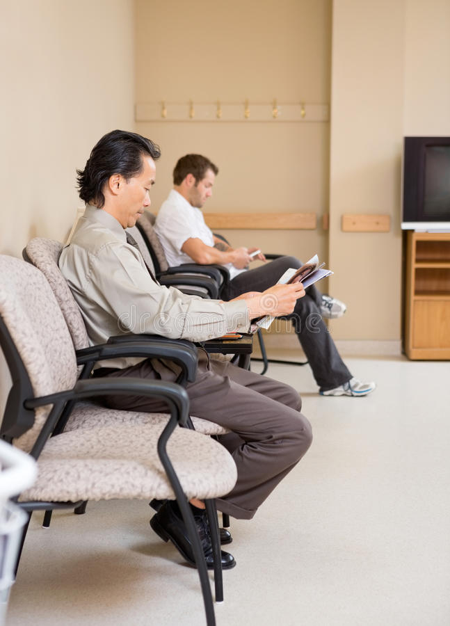 Patients Waiting In Hospital Lobby. Full length side view of patients waiting in hospital lobby stock photography