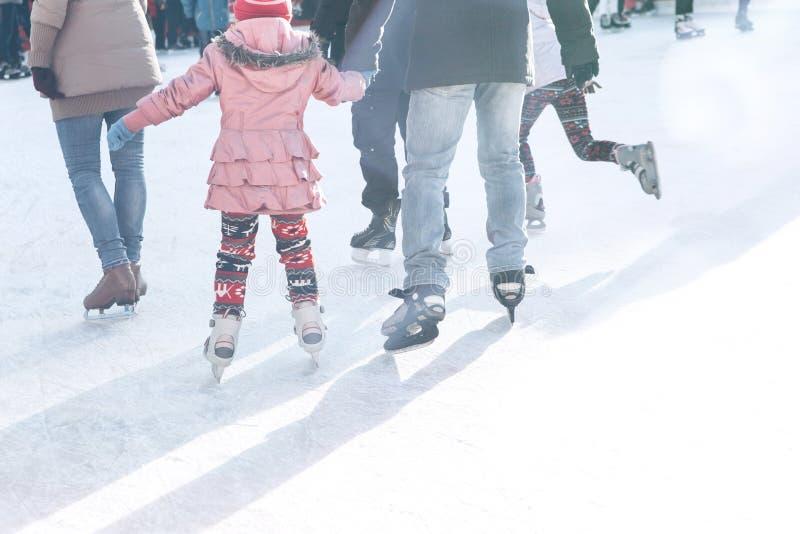 Patim do pai e da filha na pista durante os feriados de inverno foto de stock