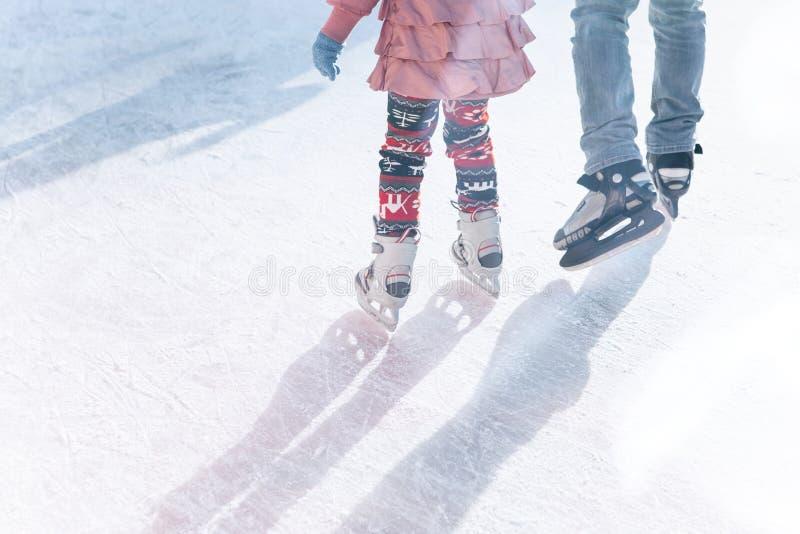 Patim do pai e da filha na pista durante os feriados de inverno imagem de stock royalty free