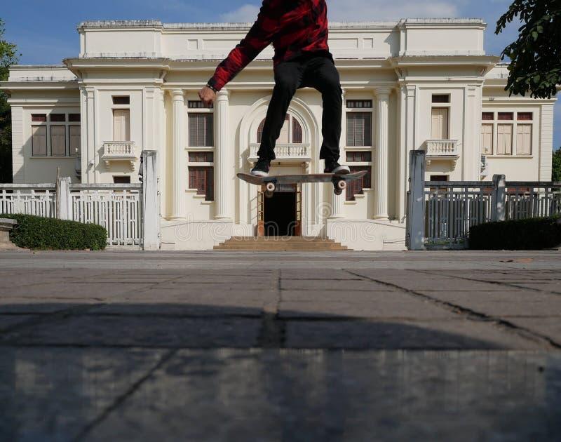 patim & salto do skater fora na frente da construção bege M fotos de stock royalty free