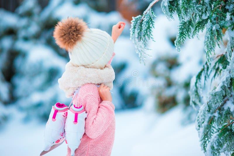 Patin allant mignon de petite fille dans le jour de neige d'hiver dehors photographie stock libre de droits