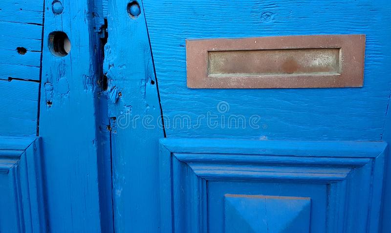 Patina Brass Mail Slot in Distressed Blue Wooden Door royalty free stock photo