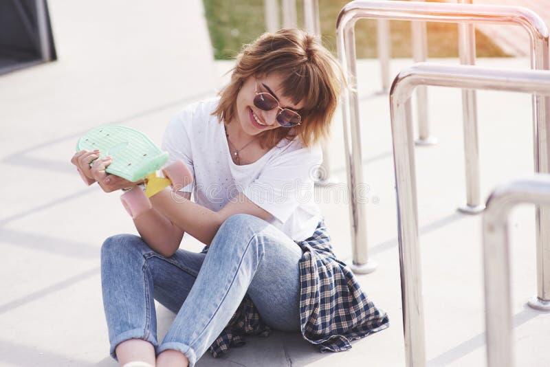 Patinador de sexo femenino adolescente hermoso que se sienta en rampa en el parque del patín Concepto de actividades urbanas del  foto de archivo libre de regalías