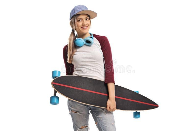 Patinador de sexo femenino con un longboard y una sonrisa de los auriculares imágenes de archivo libres de regalías