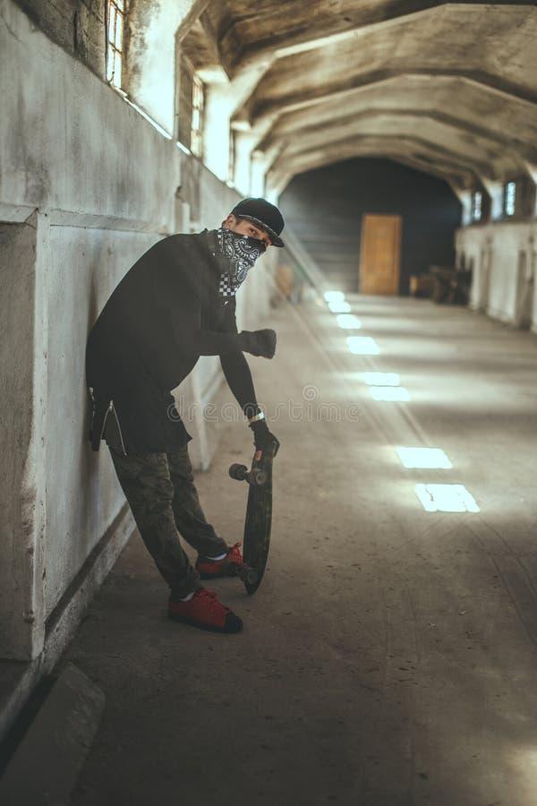 Patinador del Gangsta en máscara con el monopatín fotos de archivo libres de regalías