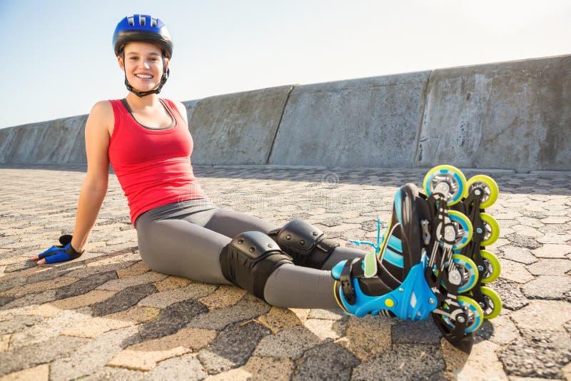 Patinador rubio deportivo sonriente que se sienta en la tierra fotografía de archivo libre de regalías