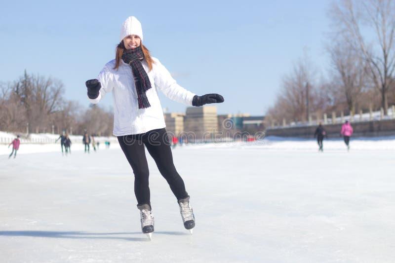 Patinage de glace attrayant de jeune femme pendant l'hiver photographie stock