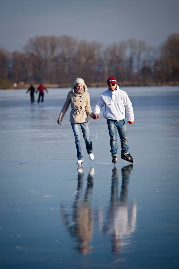 Patinage de glace de couples sur un étang images libres de droits