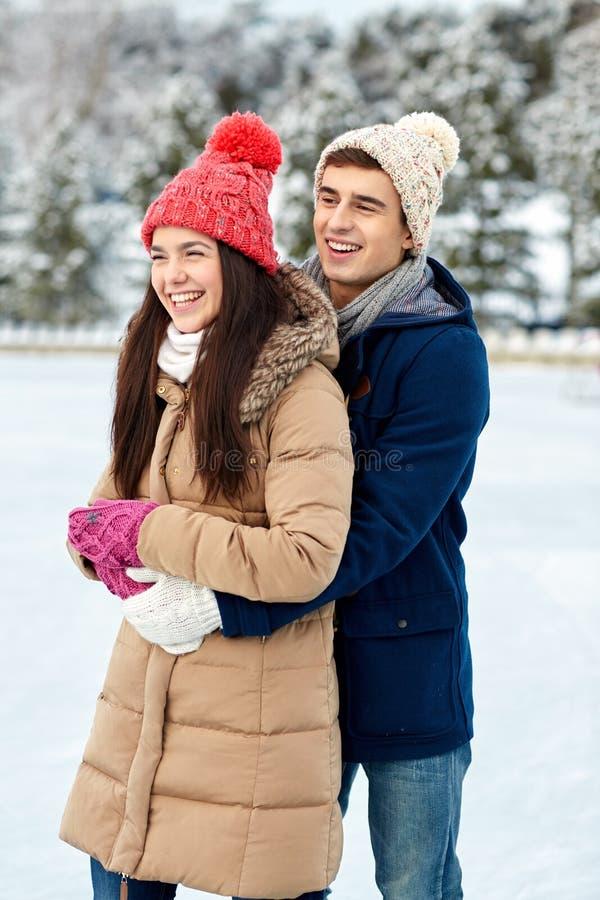 Patinage de glace heureux de couples sur la piste dehors photographie stock libre de droits