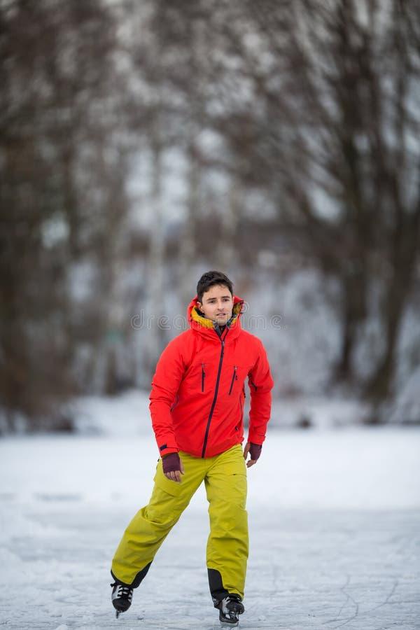 Patinage de glace de jeune homme dehors sur un étang photographie stock