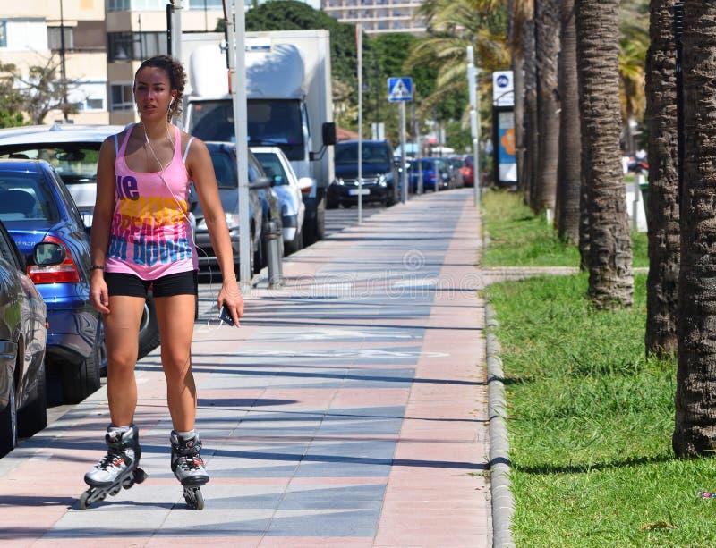 Patinage de rouleau attrayant de jeune femme le long du trottoir image stock