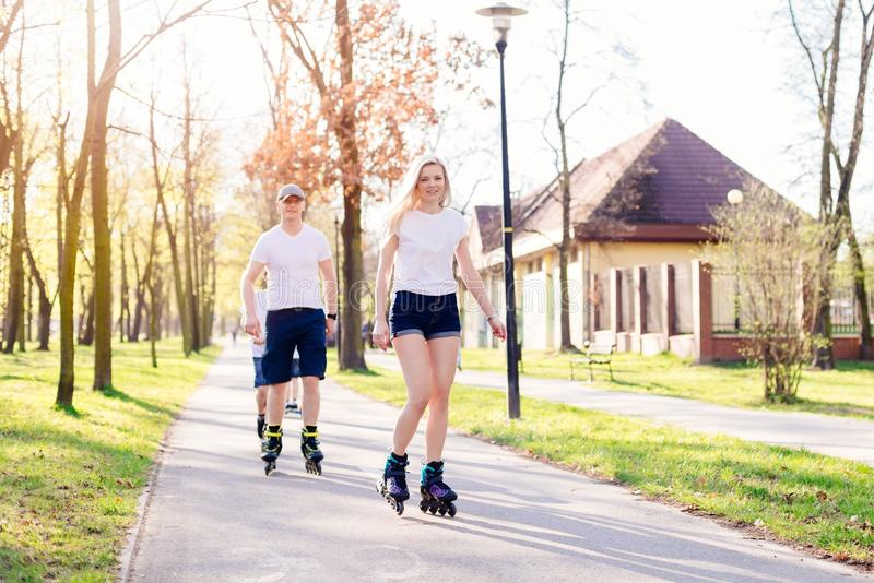 Patinage de rouleau de couples sur la route de parc photo stock