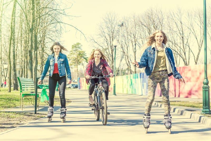 Patinage de rouleau de l'adolescence de filles et monte d'une bicyclette au parc photos stock